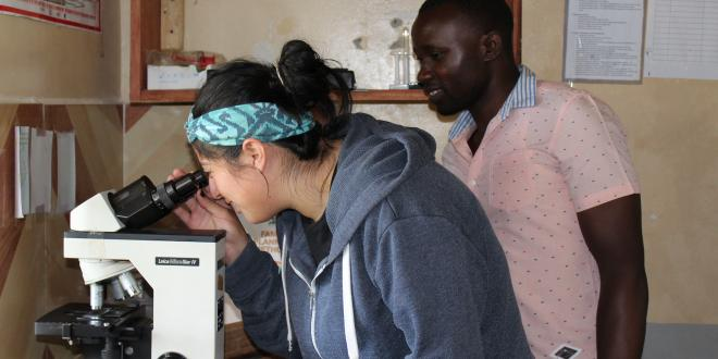 HMS student Cynthia Pando learns how to detect malaria parasites from Lab Technician Emma at a clinic on a summer experience in Bududa, Uganda. In Bududa, malaria is the leading cause of death, followed by pneumonia and diarrhea diseases.""