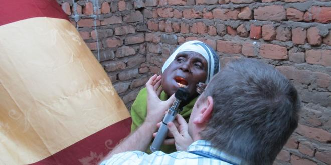 Student working with patient seeking medical treatment in Tanzania.